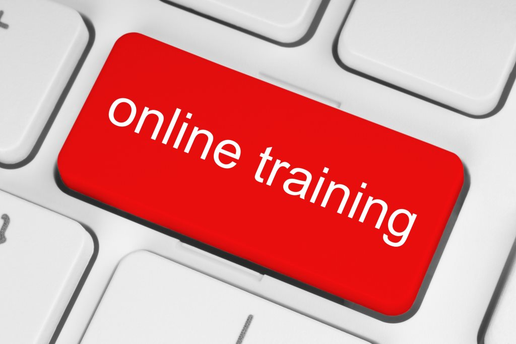Red online training button on white keyboard background